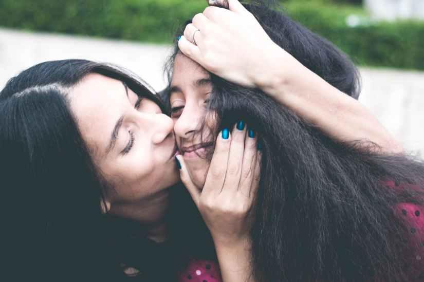 woman kissing cheek of girl wearing red and black polka dot top