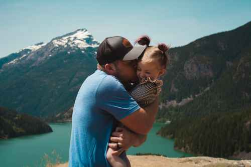man wearing blue crew neck t shirt holding girl near mountains