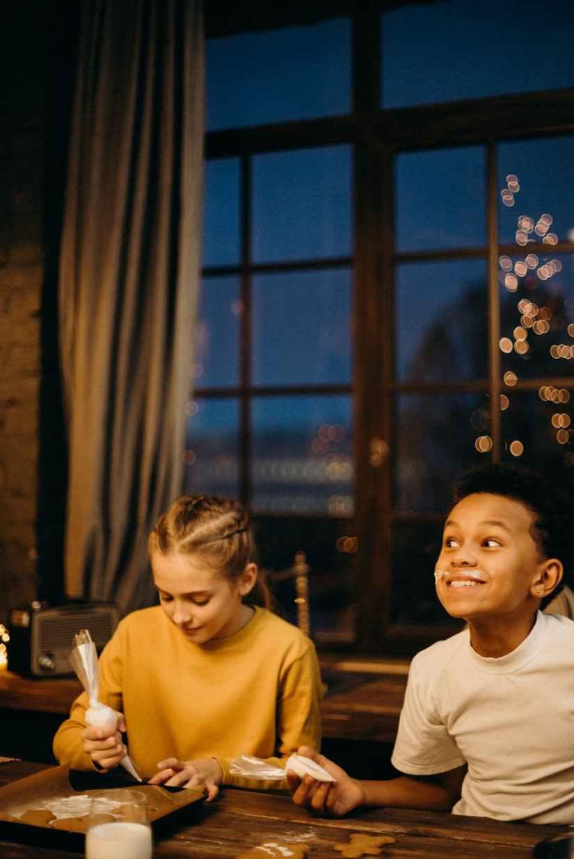 smiling boy holding sliced cake sitting near girl holding whip cream