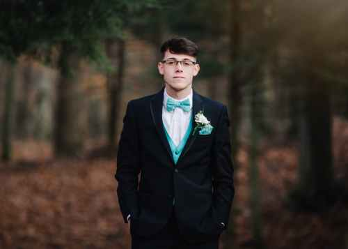 man wearing black suit jacket with teal bowtie