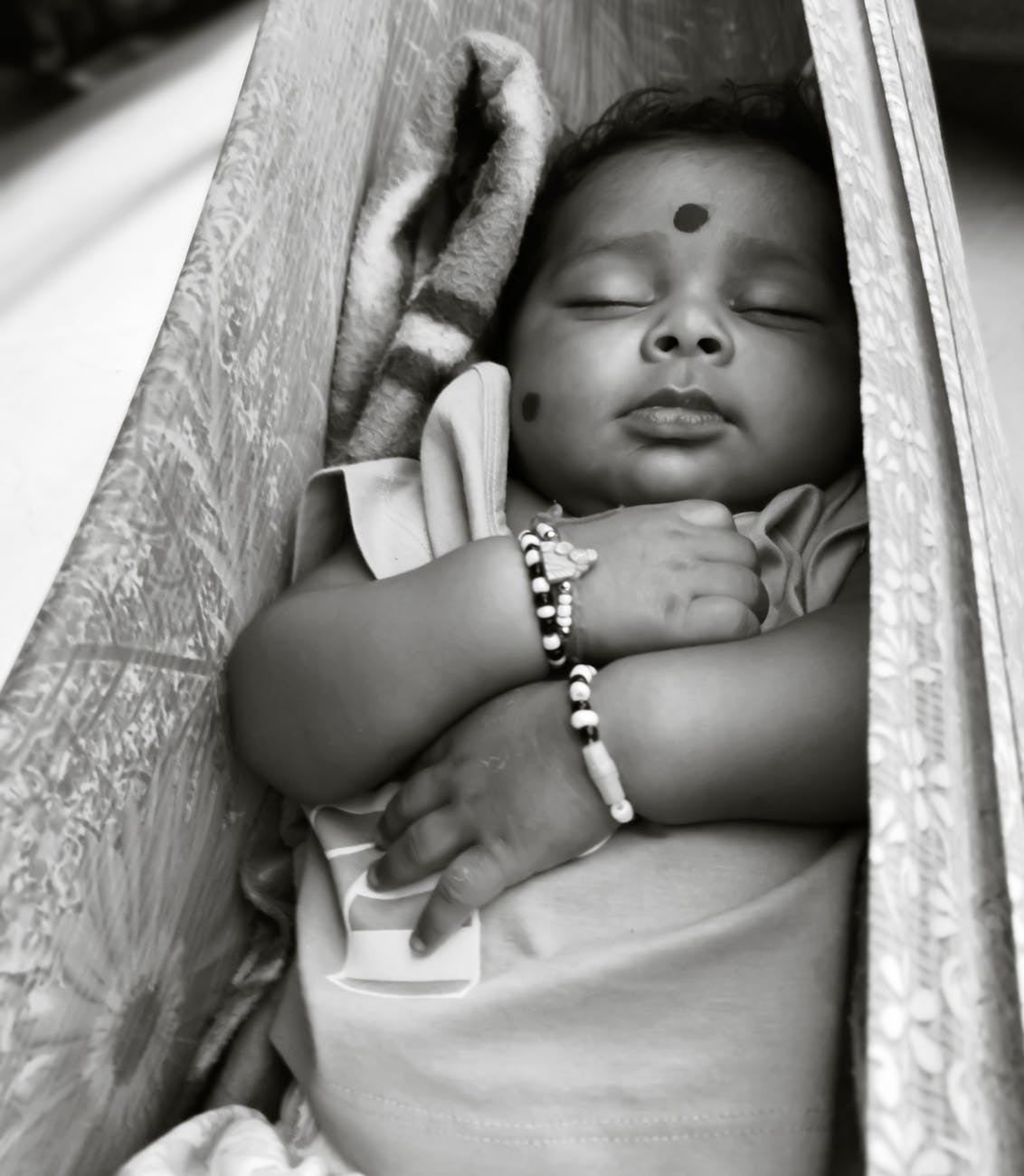 grayscale photo of baby lying on hammock
